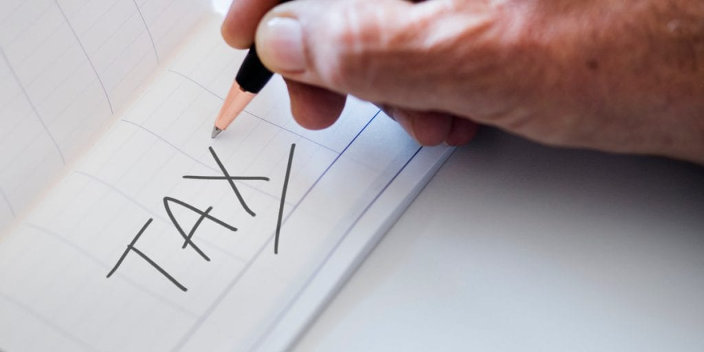 Lawyer writing the word tax onto a sheet of paper